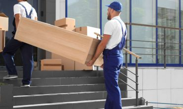1565370691332_bigstock_male_movers_carrying_shelving_258427084